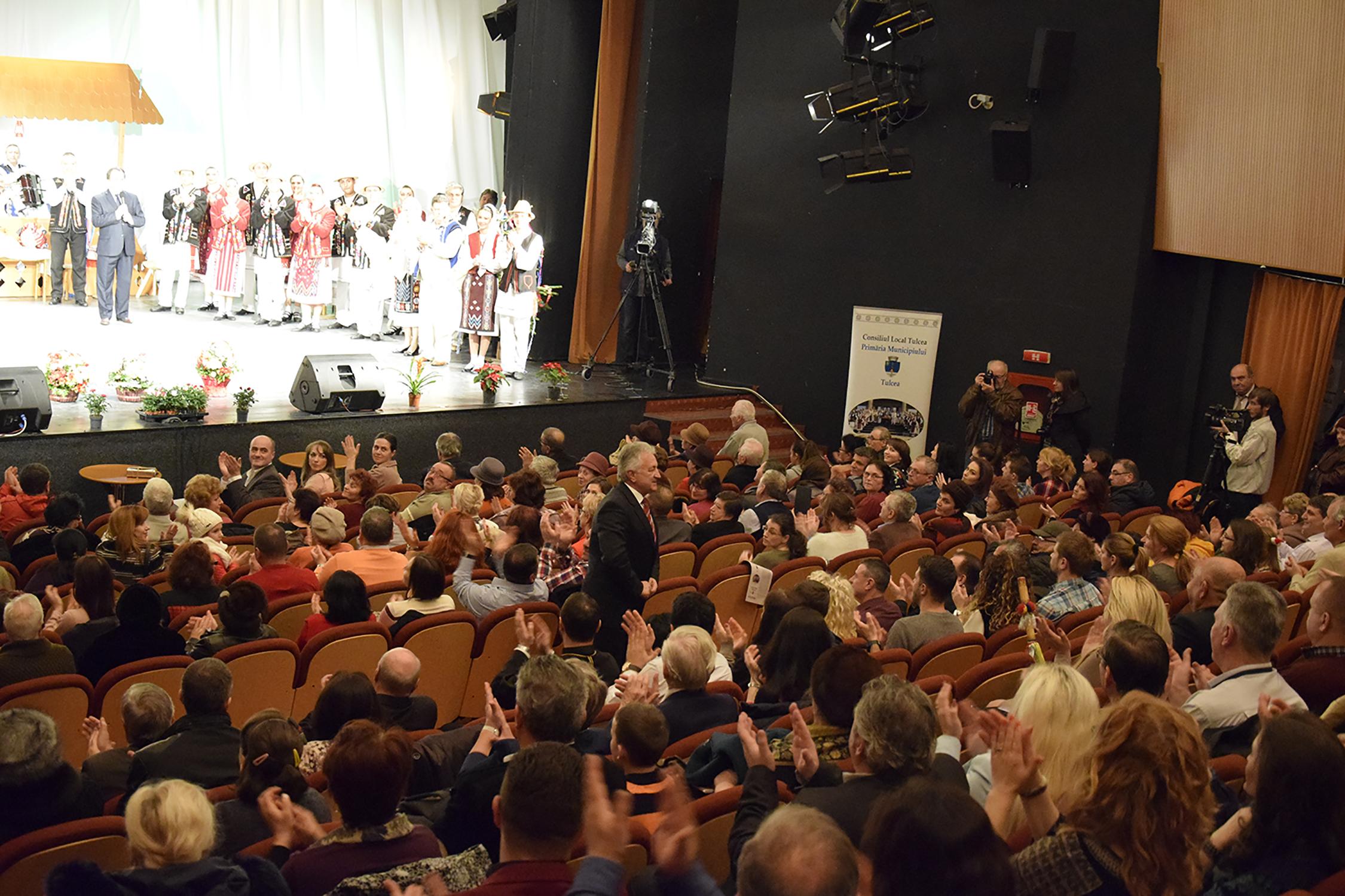 18.Sala aplaudând artiștii. Primarul Municipiului Tulcea se îndreaptă spre scenă
